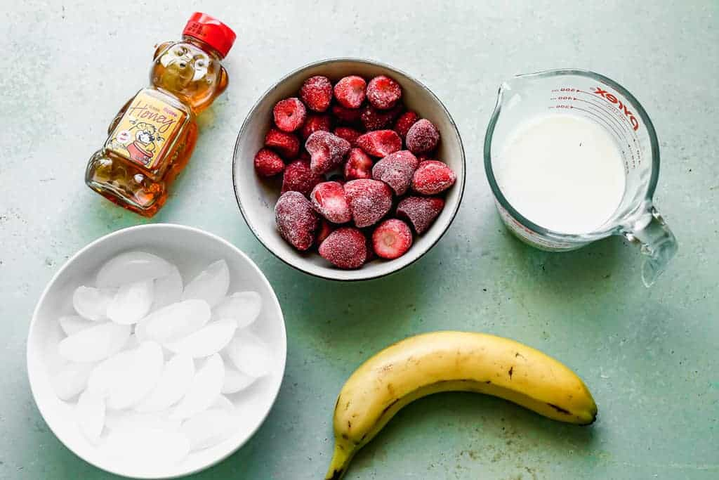 The ingredients needed to make a Strawberry Banana Smoothie.