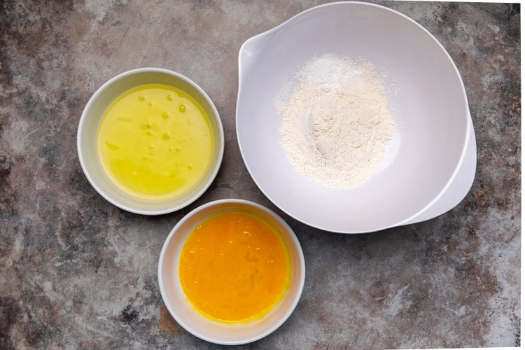 Egg whites in a mixing bowl, egg yolks in a separate mixing bowl, and flour, baking powder and salt in a third mixing bowl.