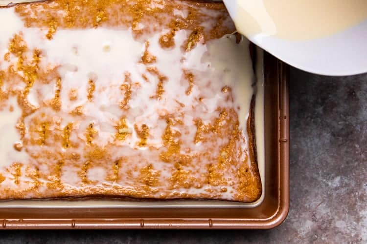Milk mixture being poured over a cake in a pan, with holes poked in the cake.