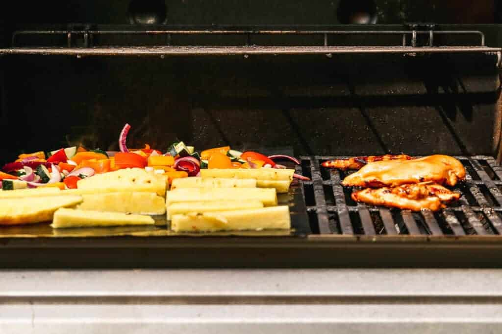 Chicken, pineapple spears, and vegetables grilling on a gas grill.