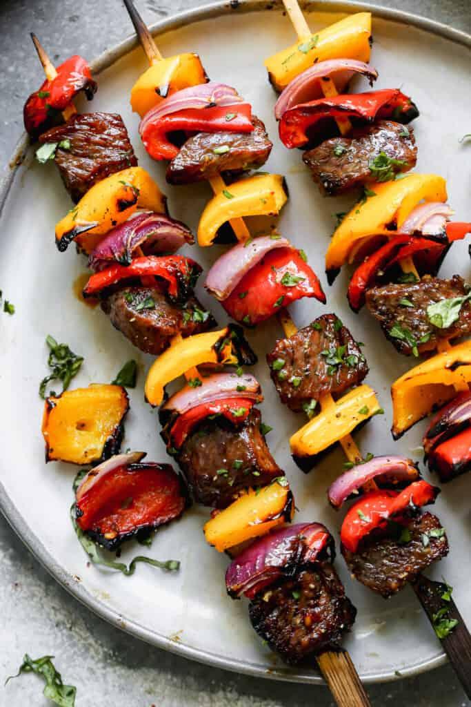Three grilled steak kebob skewers on a plate.