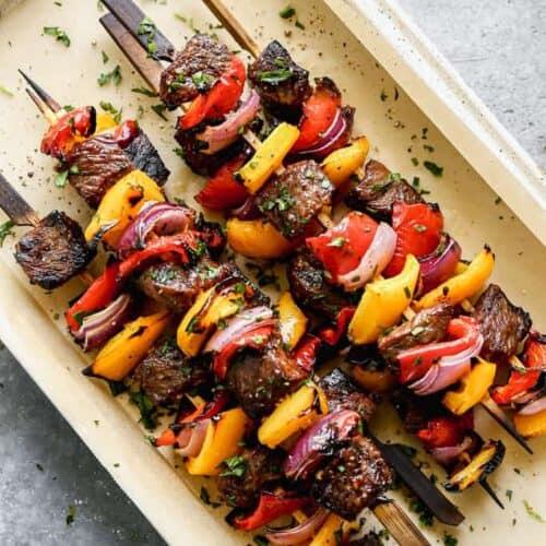 Steak Kebabs stacked on a serving platter.