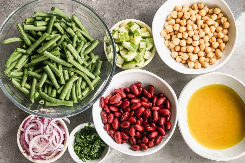 The ingredients needed to make Three Bean Salad with fresh green beans, kidney beans and garbanzo beans.
