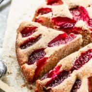 A baked plum cake with a slice cut from it.