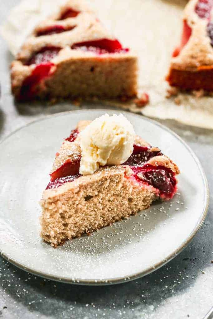 A slice of plum cake on a plate with a scoop of vanilla ice cream on top.