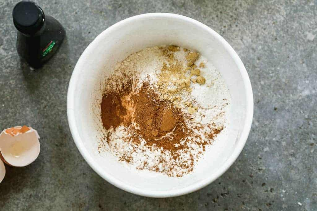 Flour, baking powder, salt, cinnamon, nutmeg, cloves and ginger added to a mixing bowl.