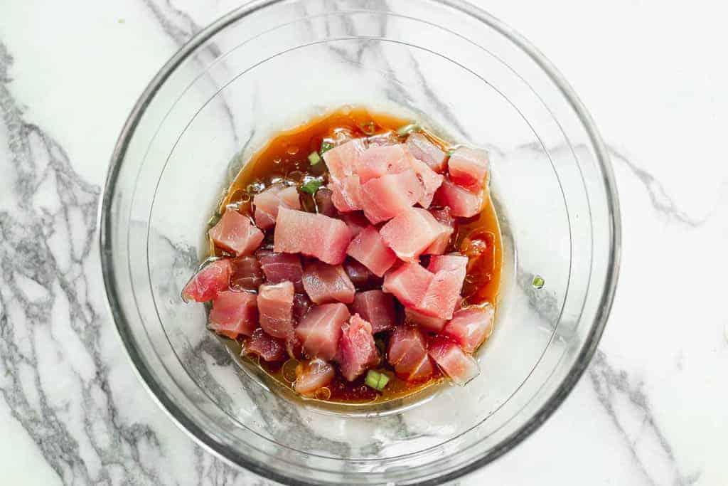 Chopped ahi tuna in a marinade for poke bowls.