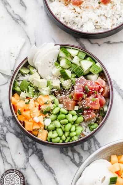 A homemade poke bowl with marinated ahi tuna, coconut rice, edamame, mango, cucumber and avocado.