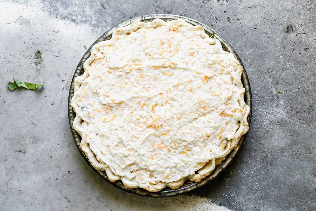 Creamy cheese layer topped on vegetable pie, ready to bake.