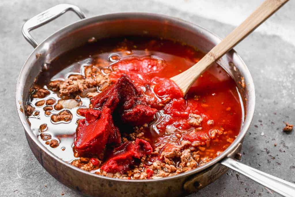 Tomato sauce, tomato paste, and broth added to cooked ground beef, onion and spices to make American Goulash.