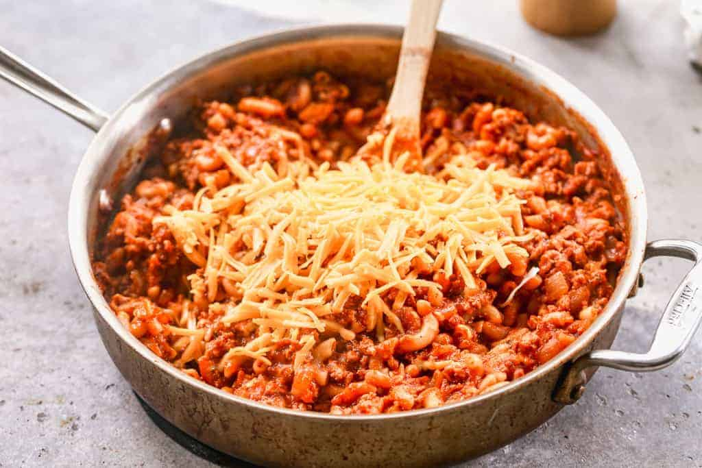 American Goulash cooked in a pan, with shredded cheddar cheese added on top.
