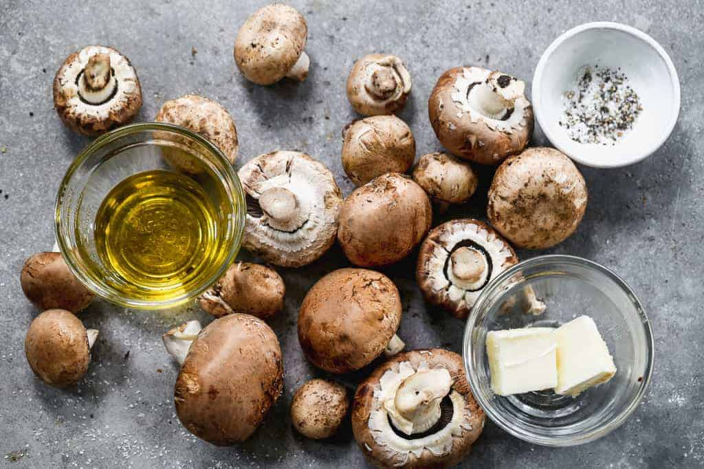 The ingredients needed to sauté mushrooms, including mushrooms, butter, oil, salt and pepper.