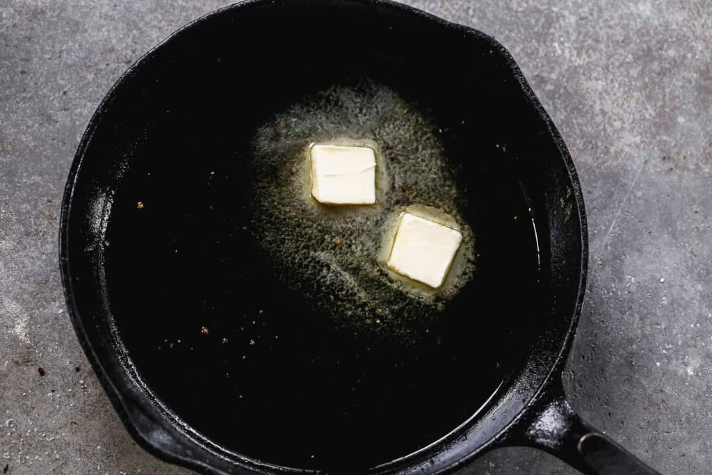 A cast iron skillet with oil and butter heating in it.