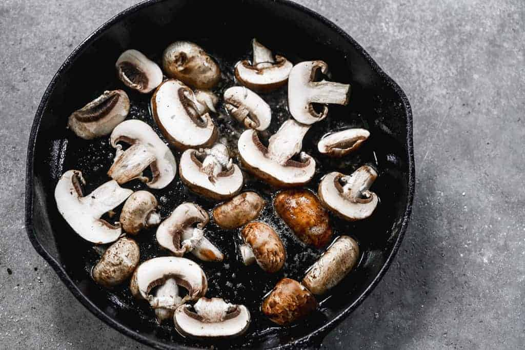 Mushroom slices in a hot pan, in a single layer, spaced apart.