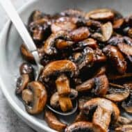A plate of sauteed mushrooms with a spoon.