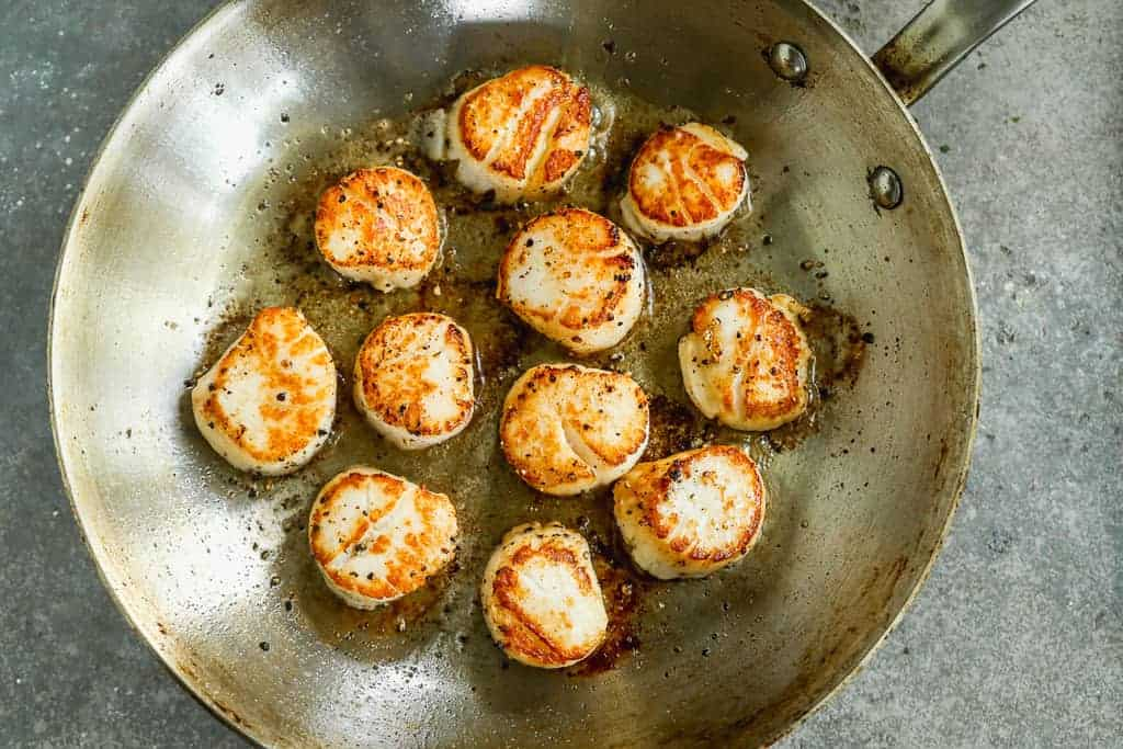 Scallops searing in a pan, flipped once to show golden crust.
