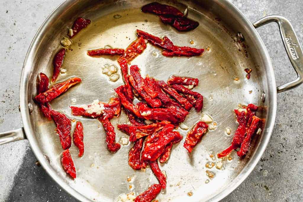 Sun dried tomatoes sautéing in oil in a skillet.