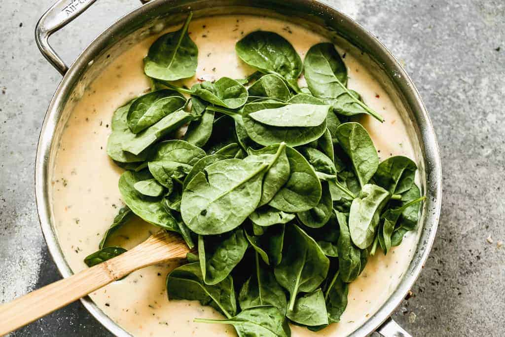 Fresh spinach added to a skillet with sun dried tomato and creamy sauce.