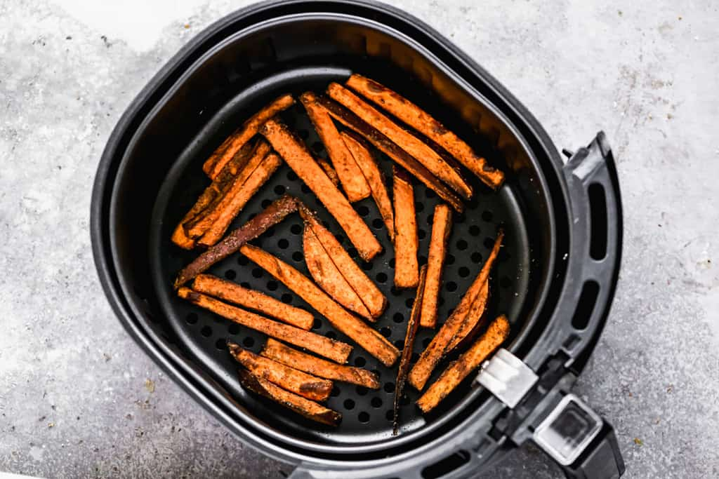 Cooked sweet potato fries in the basket of an air fryer.