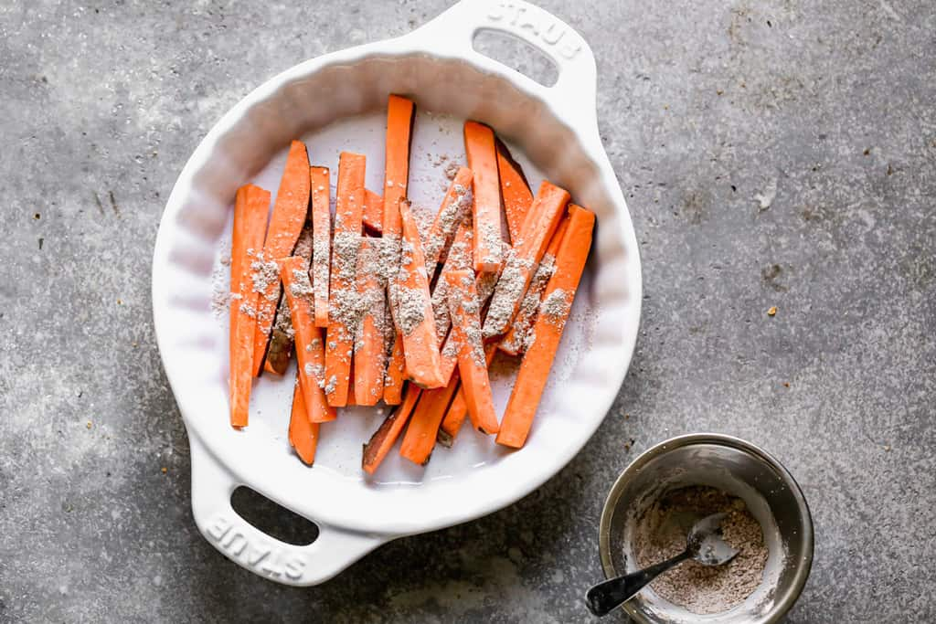 Thinly sliced sweet potatoes in a dish with seasonings sprinkled on top, to make fries.