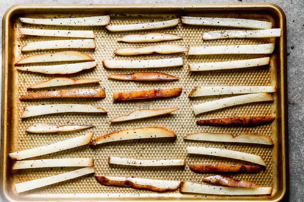 Seasoned, sliced russet potatoes lined on a baking sheet, ready to bake.