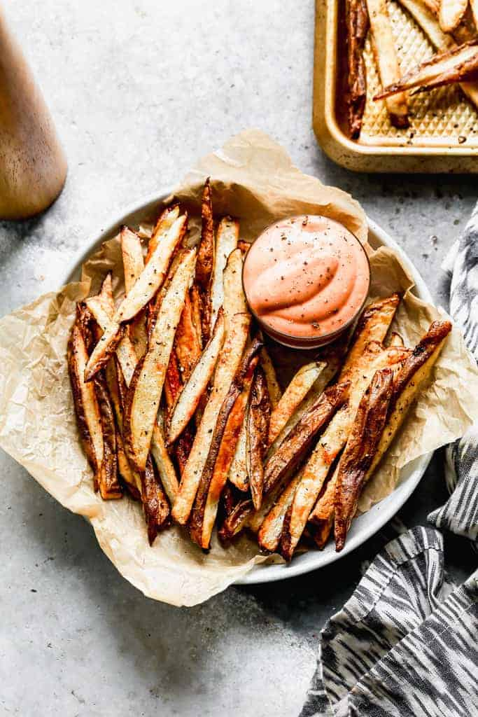 A basket of homemade french fries with fry sauce for dipping.