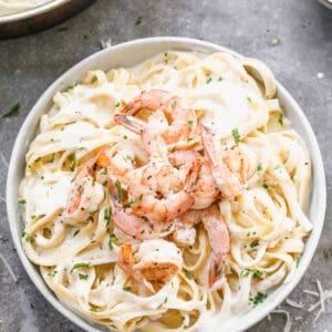 Shrimp Alfredo made with fettuccine noodles, served in a bowl