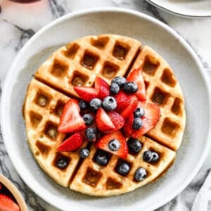 A Belgian waffle on a plate with fresh berries and syrup on top.